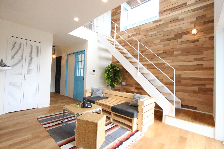 LDKは吹き抜けとスチール階段が開放感を演出。階段側の壁にはアートパネルが配置され、真っ白なリビングのアクセントに。朝から自然光を取り込む大きな窓からは海も一望できる。壁にはランダムに貼られたレッドシダーが一際目を引く