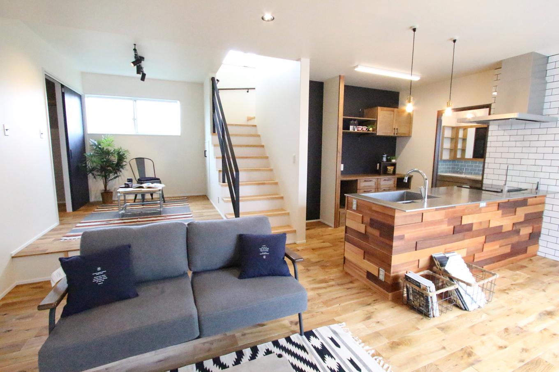 永太建工【1000万円台】リビングダイニングとキッチンは、小上がりや階段などの壁をなくしたことで広々と開放的に。どんな家具とも相性抜群のこの空間は、簡単そうで難しい床材や壁紙、ドアなどの微妙な色使いによるもの。施主さんの希望通り、まさに友達を呼びたくなる空間になった