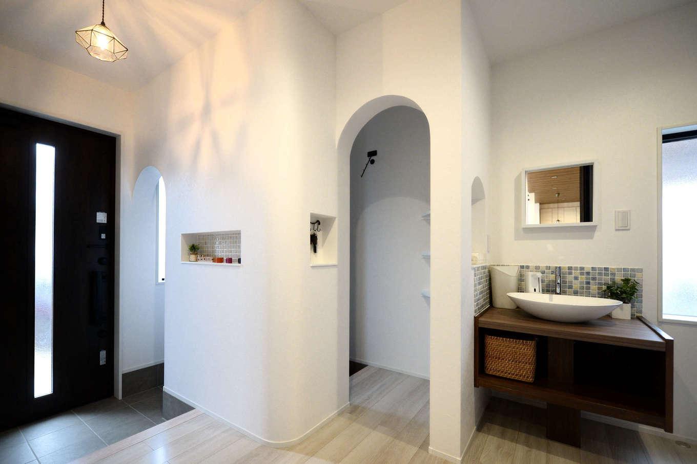 シューズクロークの出入口をアーチ状にくり抜いて、洞窟のようにデザインした玄関。壁の出隅をRにしただけで空間がやさしい雰囲気になる。3か所のニッチはすべて大きさ、デザインを変えてニュアンスを出した。木の洗面台は造作