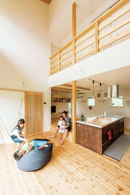 アトラス建設【デザイン住宅、自然素材、間取り】大きな吹き抜けからの光に包まれるLDK。床はすべて無垢のアカマツで、壁と天井は空気の清浄作用をもつ漆喰。キッチンは既製品に無垢板を張り、コストを抑えつつも、オリジナル感溢れる仕上がり