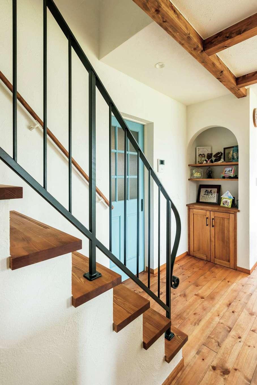 アトラス建設【デザイン住宅、子育て、趣味】リビング階段には曲線がきれいなアイアンの手すり。玄関につながる木製の引き戸は、D邸のアクセントカラーであるブルーでヴィンテージ塗装