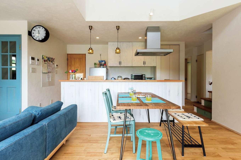 アトラス建設【デザイン住宅、趣味、自然素材】白のキッチンカウンターと収納ボードはヴィンテージ仕上げ。レトロな照明とのバランスもいい
