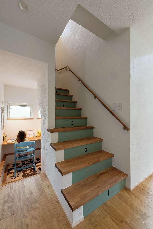 アトラス建設【デザイン住宅、趣味、自然素材】階段下のプレイルームはキッチンからも目が届く。階段には遊び心ある数字のペイントも