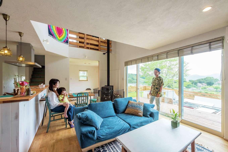 アトラス建設【デザイン住宅、趣味、自然素材】大きな開口部と吹き抜けがあるLDKは、面積以上の広がりを体感できる。リビングから庭のウッドデッキ・自作中のランプまで、外と内が一体化したかのような空間