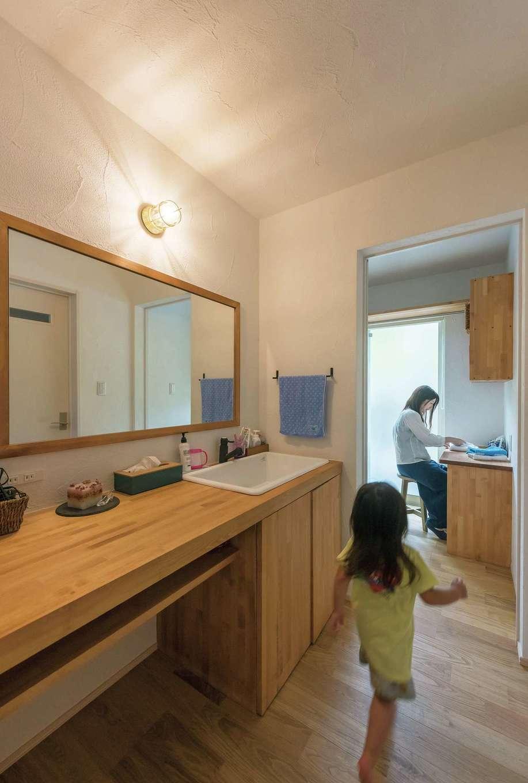 アトラス建設【デザイン住宅、趣味、自然素材】オリジナル洗面台の奥には家事室。調湿効果のある漆喰壁だから、室内干しもスッキリ