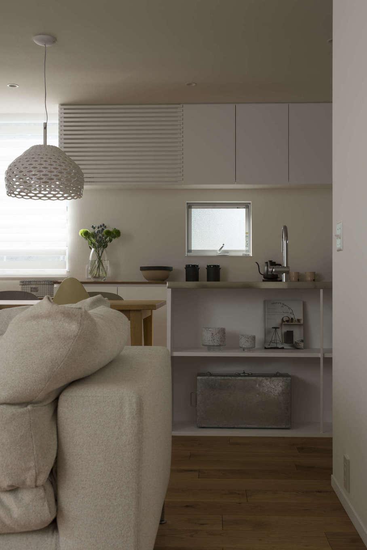 白で統一したキッチンに、ペンダント照明も白をコーディネート。前面の棚には、リビングからの視線を意識してオシャレな小物をディスプレイ。カウンターの厚みや棚の仕切りの幅など、細部まで計算し尽くされたデザインが、簡潔で美しい空間を創り出している