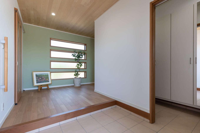 家の「顔」である玄関はゆったり広々と確保。4連のスリット窓から射し込む淡い光が空間をやさしく包み込む。奥さまの祖母が遺したちぎり絵の美しい風景画がゲストをあたたかく迎える