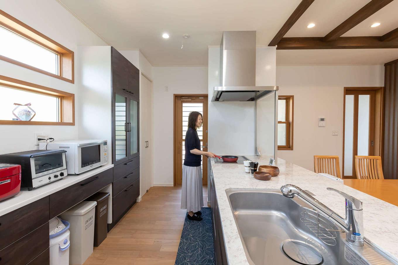 奥さまの憧れを叶えたアイランドキッチン。大理石の広いワークトップは作業しやすく、ご主人も手伝いやすい。北面にも窓を設け、明るい空間で料理できるのがいい。ぐるぐると回遊できるので、奥さまの家事効率もグーンとアップ!