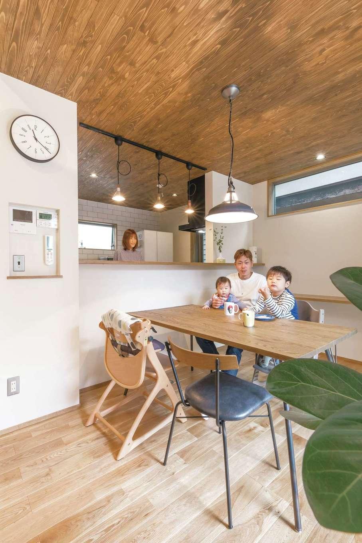 小玉建設【デザイン住宅、趣味、ガレージ】南面の開口からたっぷり陽が入る明るいDK。東西に隣家が接近しているため、窓の位置にも配慮。床、天井、家具に無垢を使い、金属の照明がアクセントに