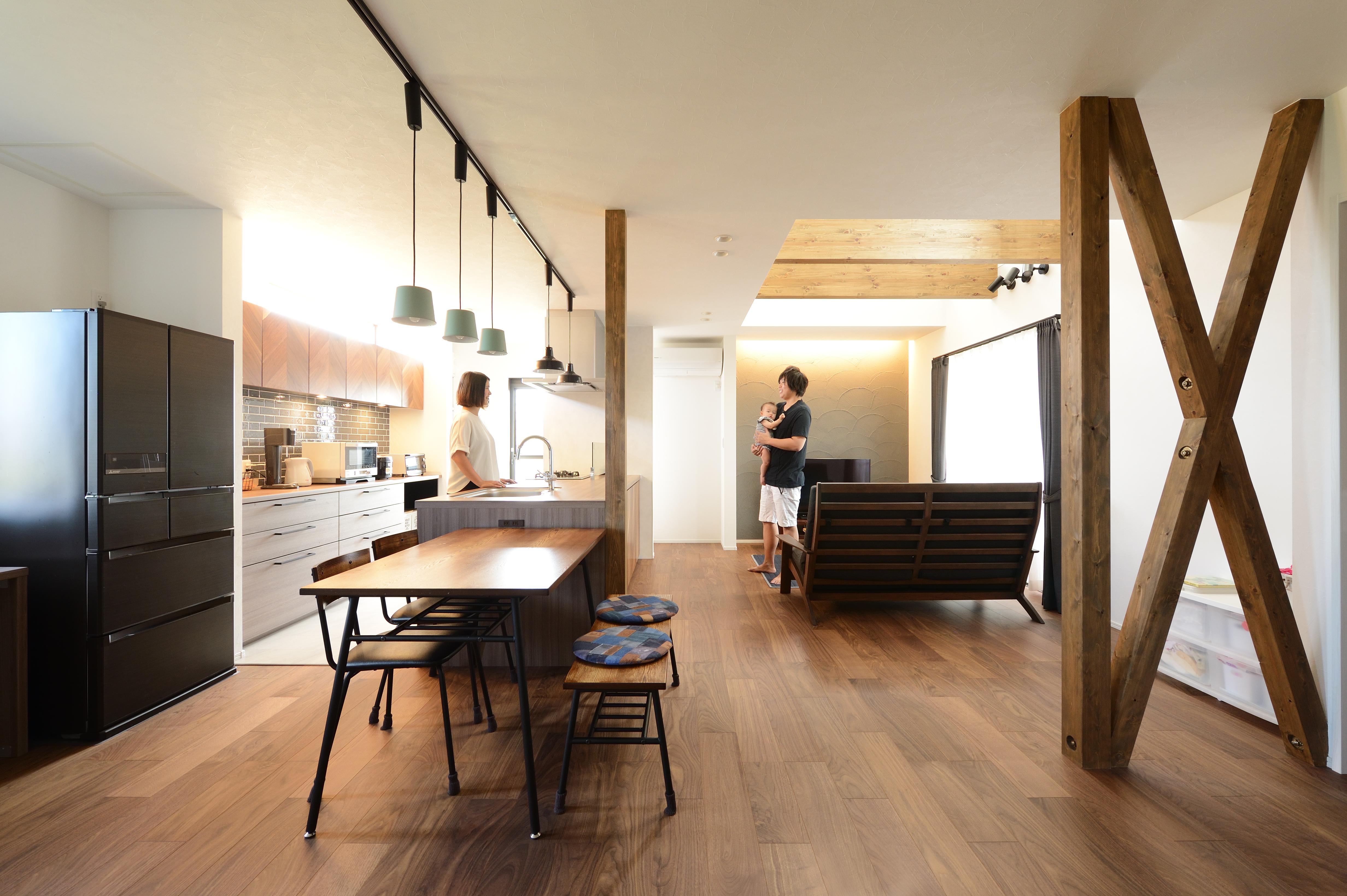 アルファホーム【デザイン住宅、子育て、インテリア】パッと目をひくデザインのキッチンはLDK全体を見渡せる位置に計画。 木目柄を中心としてコーディネートし、特にヘリンボーン柄の扉がポイント。