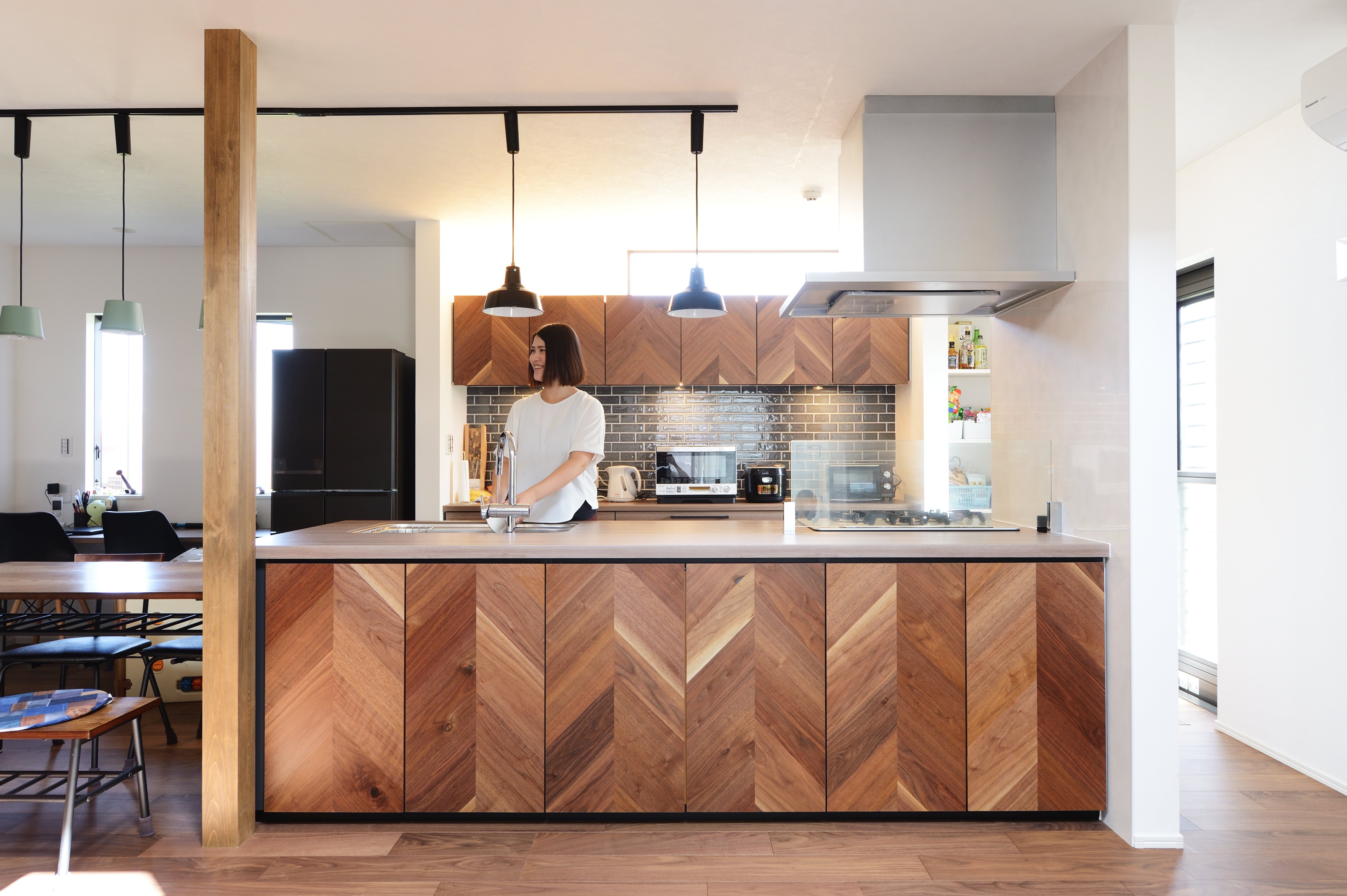 アルファホーム【デザイン住宅、子育て、インテリア】お揃いのヘリンボーン柄のカップボードも設け、壁をタイルで仕上げたのもコーディネートのポイント。キッチン収納の取っ手は奥様のこだわりのもの