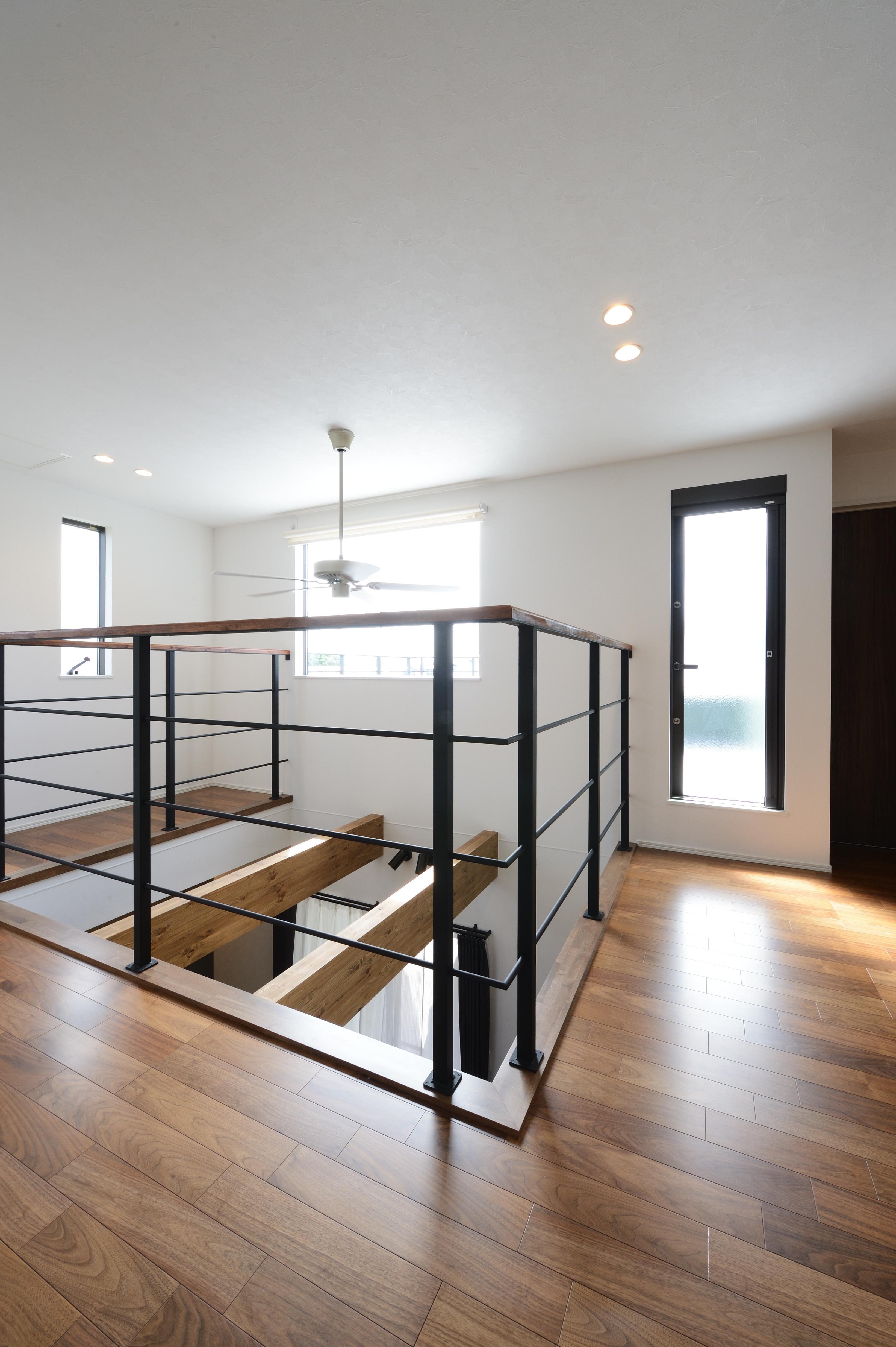 アルファホーム【デザイン住宅、子育て、インテリア】吹き抜け周りは壁をつくらずアイアン手すりで仕上げ、目線が通るよう設計。お部屋のアクセントはもちろん、目線が抜けるので開放的。吹抜けを囲んでいるアイアン手すりは上部だけ床色に合わせた木で仕上げた