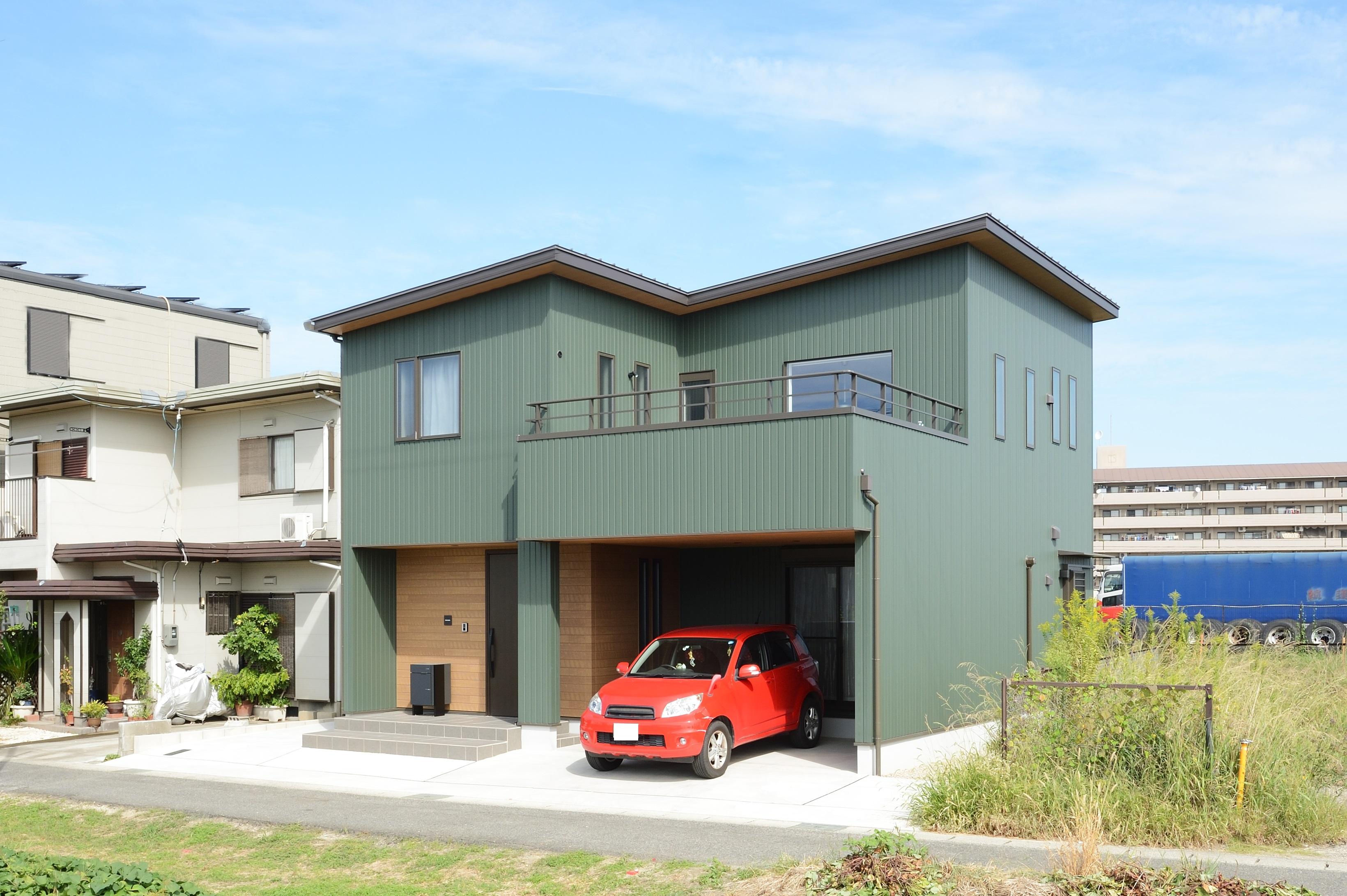 アルファホーム【デザイン住宅、子育て、インテリア】外装は緑色のガルバリウムで、車の色と風景を加味して決定。ガレージ上の二階にあるバルコニーでは、バーベキューが出来る