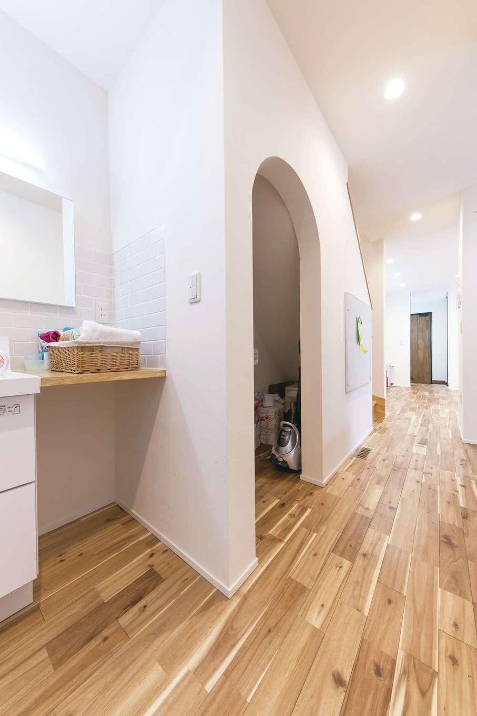 低燃費住宅 静岡(TK武田建築)【子育て、省エネ、間取り】玄関から洗面、トイレ、浴室まで一直線に続く「ただいま動線」が子どもの自主性を促す。階段下の壁をアーチ状にくりぬいて収納に