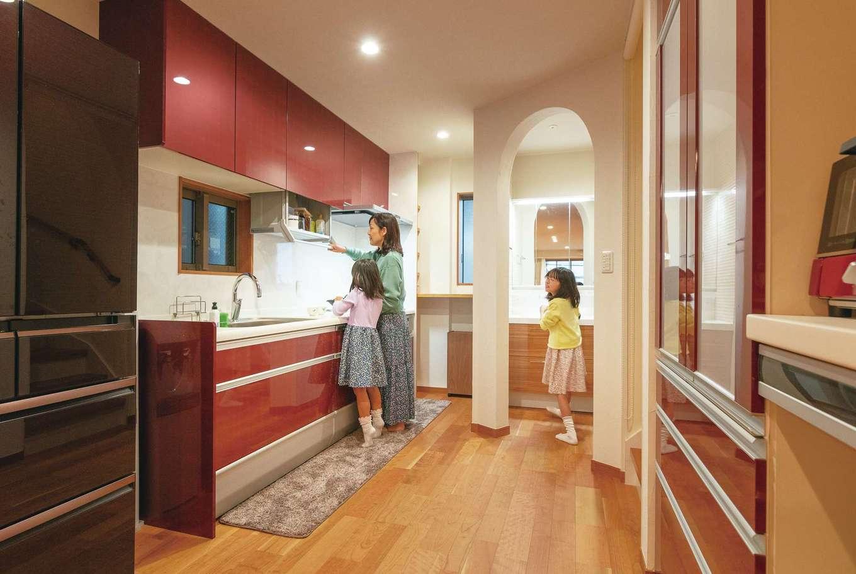 アトリエサクラ【子育て、狭小住宅、屋上バルコニー】奥さまが好きな赤で揃えたシステムキッチン。アーチ壁の向こうは洗面洗濯室とトイレ。親子揃ってキッチンに立ってもゆとりの空間には家族も感激