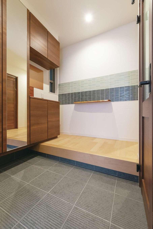 玄関を入ると目に飛び込んでくるのは、正面の壁に配したモダンなタイル使いと、素材から選んだ趣ある一枚板のカウンター。1階は和を意識したコーディネートでまとめている