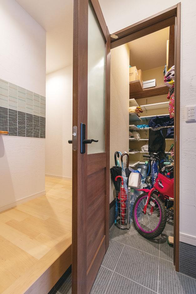 アトリエサクラ【子育て、狭小住宅、屋上バルコニー】玄関の土間収納は、コの字型に可動棚を設置。子どもの自転車もしまっておける大容量が嬉しい。落ち着きある扉を閉めれば、来客時も安心