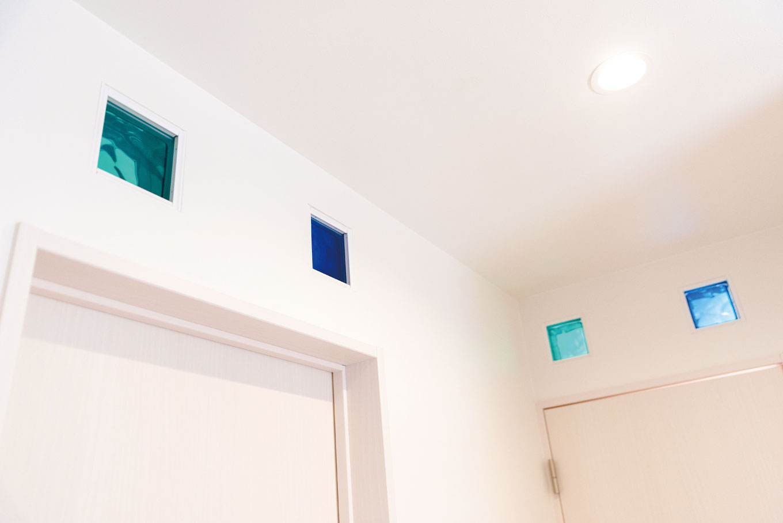 甲静ハウジング【デザイン住宅、子育て、収納力】各部屋の入口や2階廊下には、ガラスブロックがちりばめられている。カラフルな色彩がシンプルな空間のアクセントに