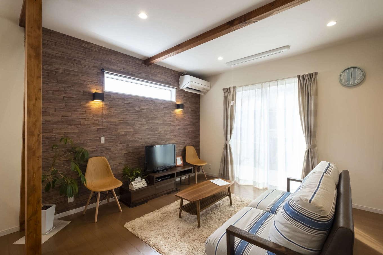 Art Wood Home (永建)【輸入住宅、間取り、自然素材】テレビボード背面の壁の木目と、ブラケットライトがムーディーな雰囲気を醸し出すリビング。自然光が優しく差し込む横長窓もおしゃれ
