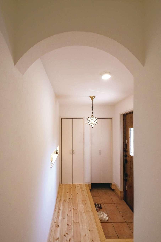 イーホーム【輸入住宅、狭小住宅、間取り】アール開口がかわいらしい玄関ホール。正面右側の扉を開けると、2.6畳の土間収納。左の扉は掃除機収納スペースになっている