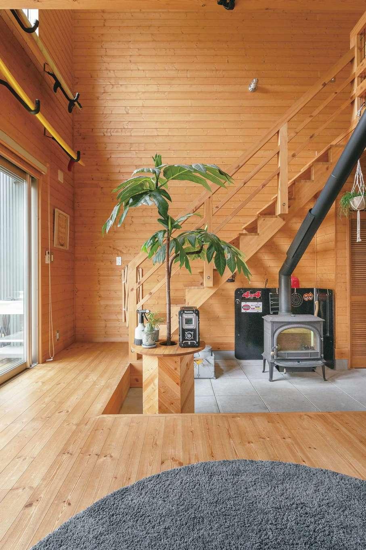 BESS浜松【子育て、収納力、インテリア】薪ストーブの上にコーヒーを置いてお茶することも多いという夫婦。だから、土間はくつろぎスペースとして座れるくらいの高さに調整した。インテリアの緑が木の空間を引き立てる