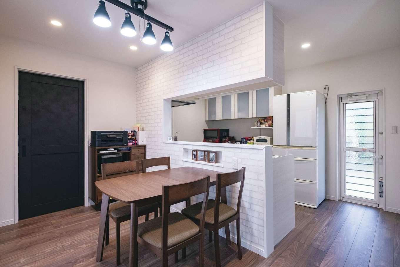 アフターホーム【デザイン住宅、間取り、ガレージ】タイル調のクロスがかわいい対面キッチン。左奥のドアを開けるとサニタリーへ