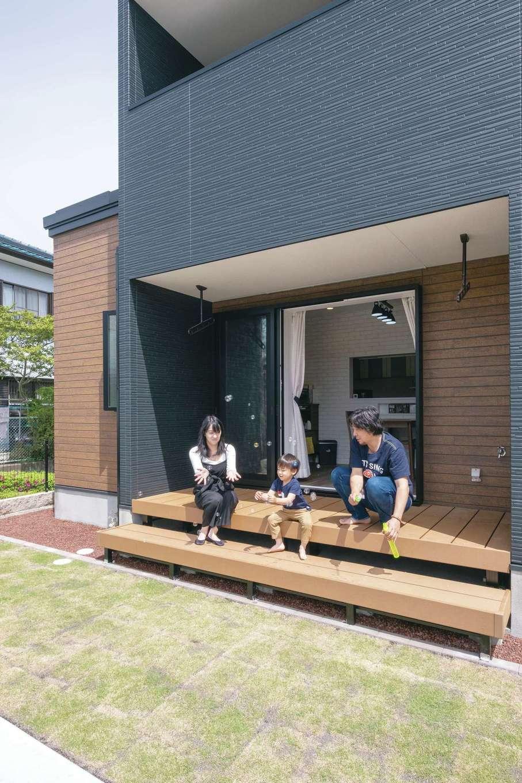 アフターホーム【デザイン住宅、間取り、ガレージ】リビングの全開口サッシを開けると、大きなウッドデッキと庭へ。休日はBBQやプール遊びを楽しむ