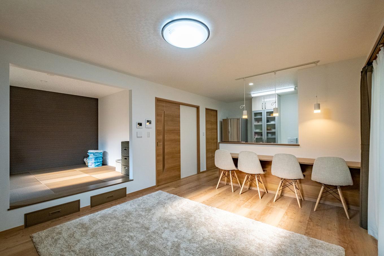 建築システム(狭小住宅専門店)【自然素材】リビングを広くするために、キッチンの壁にカウンターを付けてダイニングスペースを省略。足が当たるなどして傷みやすいカウンター下にはフローリングの端材を貼り、お洒落と実用を兼ねている