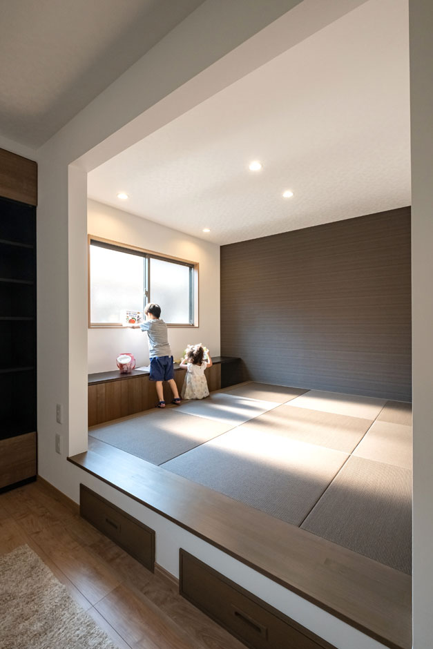 建築システム(狭小住宅専門店)【自然素材】モダンに調えた和室の下部には引き出し収納を。キッチンからも目が届くカウンターは、子どもの勉強やパソコン作業を想定して造作。一面にはリビングと同じアクセントクロスを採用して空間の調和を図っている