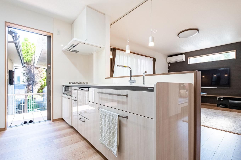 建築システム(狭小住宅専門店)【自然素材】傷が付きにくい天板など性能を重視して選んだキッチン。リビングから和室まで目が行き届く。リビングから続くウッドデッキには、キッチンのドアからも出入りできるので便利