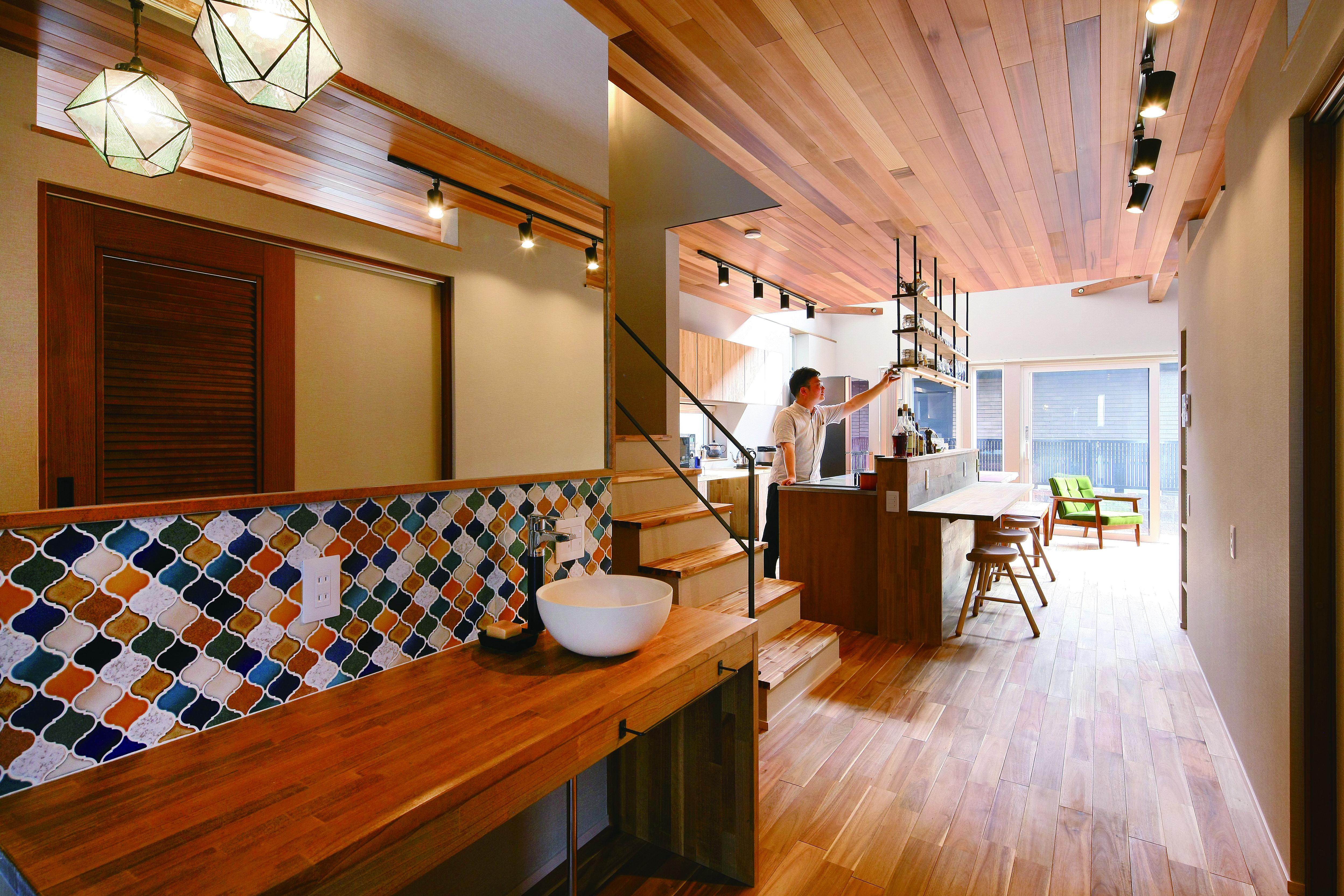 共感住宅 ray-out (レイアウト)【デザイン住宅、子育て、趣味】玄関土間とLDKの床はフラットにつながり空間をより開放的に。手洗いスペースのコラベルのタイルはご主人のこだわり