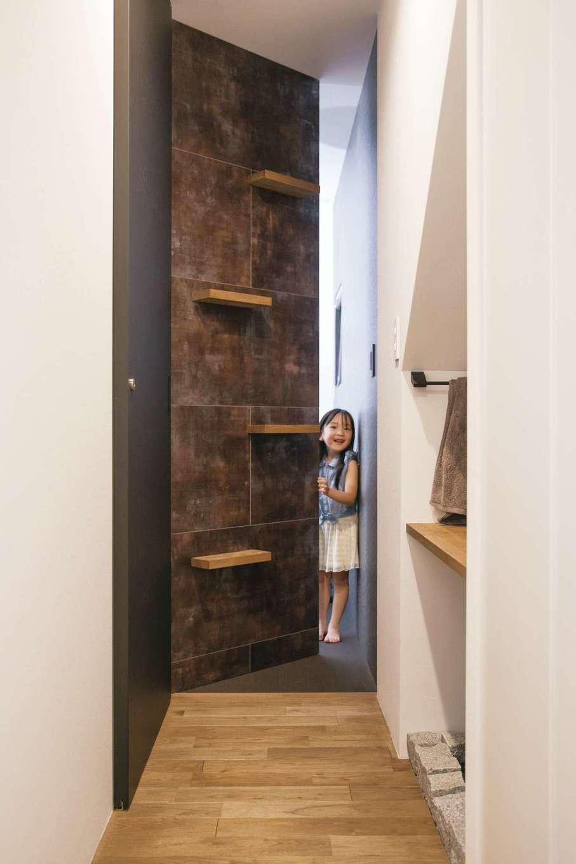 インフィルプラス【デザイン住宅、子育て、間取り】玄関の廊下の突きあたりにある壁は、実はご主人のアトリエに通じる隠し扉。内土間付きのアトリエは、ご主人の仕事場兼プライベートルーム。床はブラックの畳敷き