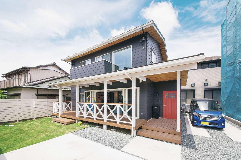 白い梁と柱が映え、玄関ドアの赤がアクセントに。夏には庭でバーベキューやプールをする予定!