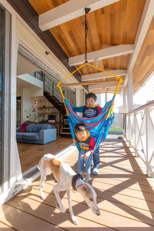 夫妻たっての希望で実現したカバードポーチ。屋根付きなので、子どもたちは雨の日でも外遊びを楽しめる。晴れた日にはハンモックを吊るし、交代でゆらゆら揺らして大はしゃぎ