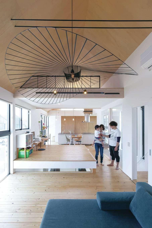MABUCHI【デザイン住宅、建築家、インテリア】強烈なインパクトがある直径2mのペンダントライトは、新婚旅行で行ったフィンランドの雑貨店で見たものを直輸入。ハンス・J・ウェグナーのロッキングチェア、アルネ・ヤコブセンのドロップチェアなど、ご主人が買い集めた北欧家具が空間のデザイン性をより高める。やさしい肌触りの床は無垢の杉板、シンプルな質感が美しい天井はラワン材。約30畳の大空間に、やわらかな光があふれ心地いい風がそよぐ