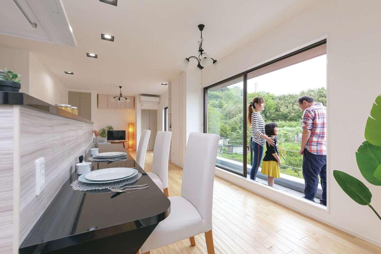 明るく開放的なLDKはアイランドキッチンを主役にプランニング。狭くなるのでダイニングテーブルは置かず、カウンターで食卓を囲むスタイルに。窓の外には緑豊かな山の景色が広がり、料理タイムもより楽しくなりそう。壁は調湿効果にすぐれた漆喰を標準で使用