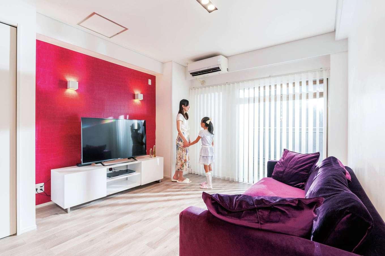 グレーの無垢の床にテレビステーションの赤いクロスが映えるイタリアンモダンのリビング。ソファとAVボードも『納得』オリジナル