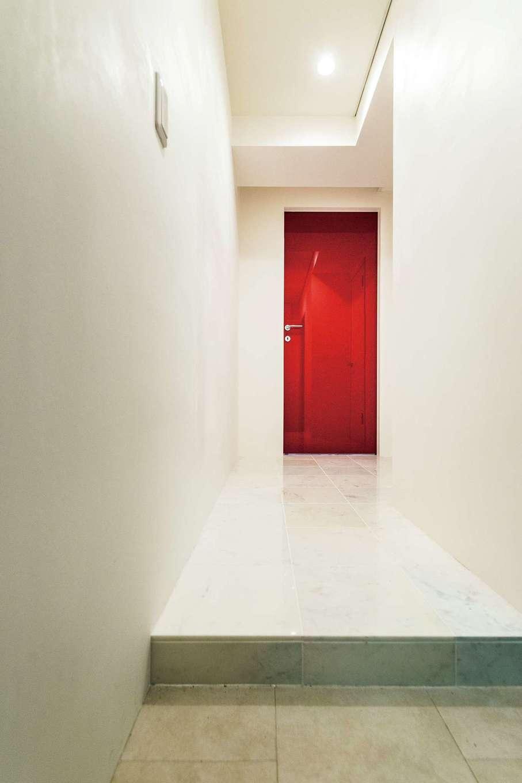 大理石タイルを貼って上質な空間に生まれ変わった玄関ホール。鏡面のように輝くデザイナーズドアは『納得』オリジナルで、イタリアを代表するデザイナー、アントニオ・チッテリオ作
