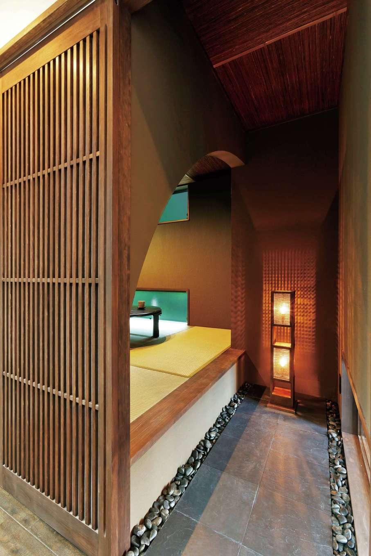 納得住宅工房【デザイン住宅、二世帯住宅、間取り】タイルを貼った前室付きの和室は二世帯共有。アール状にくり抜いた壁が隠れ家的な雰囲気を演出