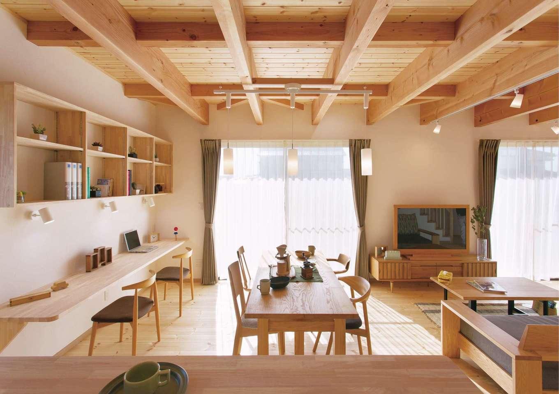 住まいるコーポレーション【デザイン住宅、自然素材、省エネ】キッチンから眺めたリビングダイニング。対面キッチンのカウンターはちょっと高めにして、作業スペースが見えないように配慮