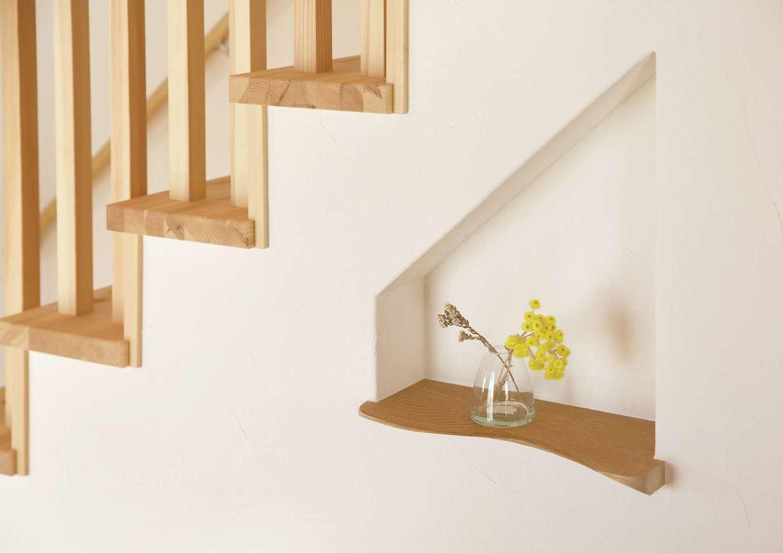 住まいるコーポレーション【デザイン住宅、自然素材、省エネ】奥さまの希望でリビングの階段下の壁に設けたニッチ。珪藻土と無垢のカウンターが調和して、小物がオシャレに映える。時計や携帯などを置くのにも便利