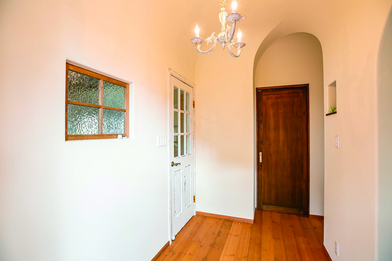 フェアリーホーム【デザイン住宅、輸入住宅、平屋】玄関の壁・天井はアール加工してほら穴のような空間に。リビングに通じる飾り窓がかわいい
