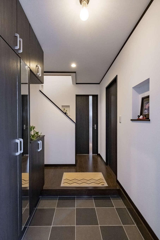 収納や鏡が備えられ、機能的にまとめられた玄関。チェック柄に配置したタイルはポーチから連続し、一体感と広がりが生まれている