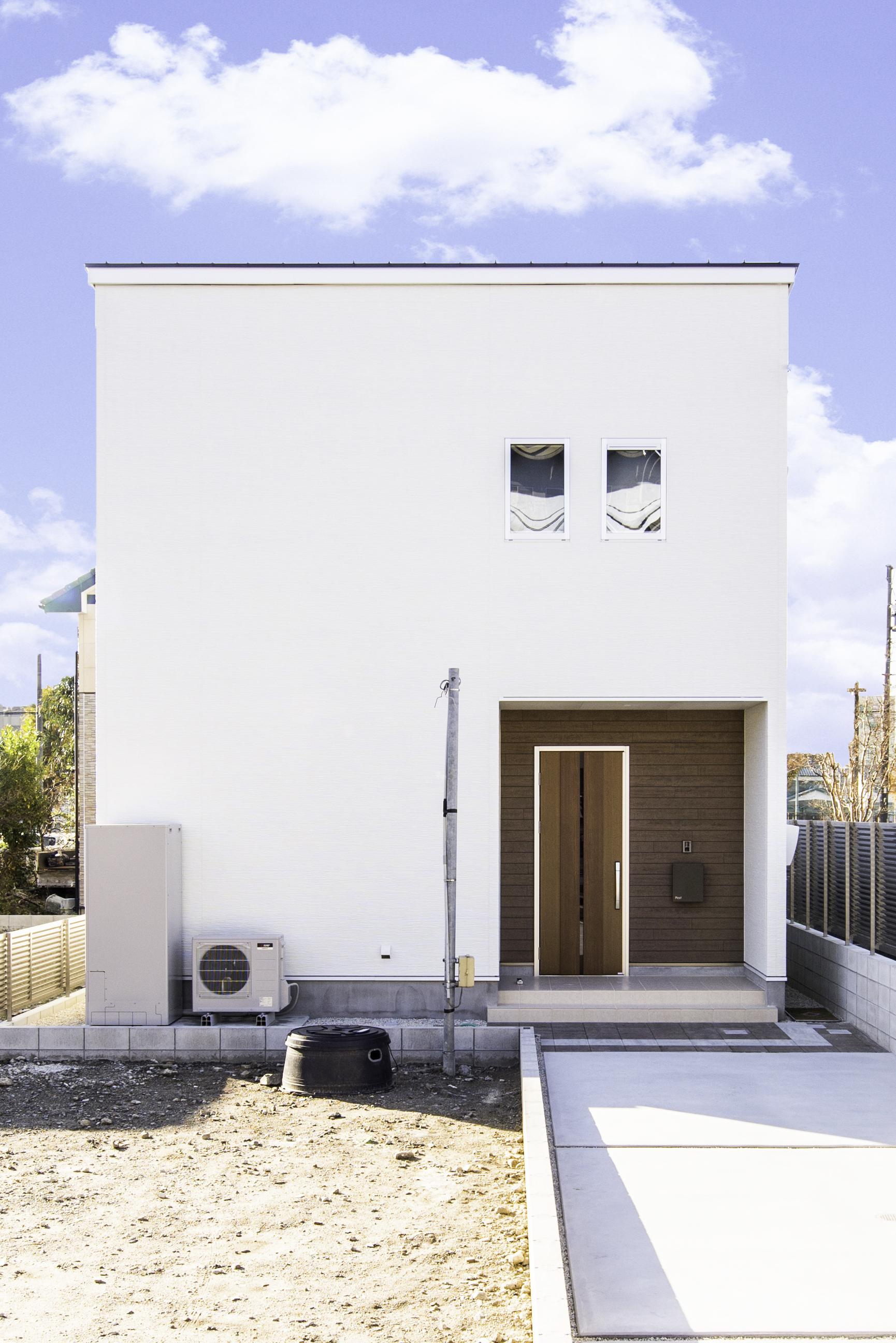 カナルホーム【1000万円台、デザイン住宅、夫婦で暮らす】外観はシンプルなキューブ型で、白と木目調のサイディングが程よく調和している。同社の家は全棟長期優良住宅認定、耐震等級3が標準仕様