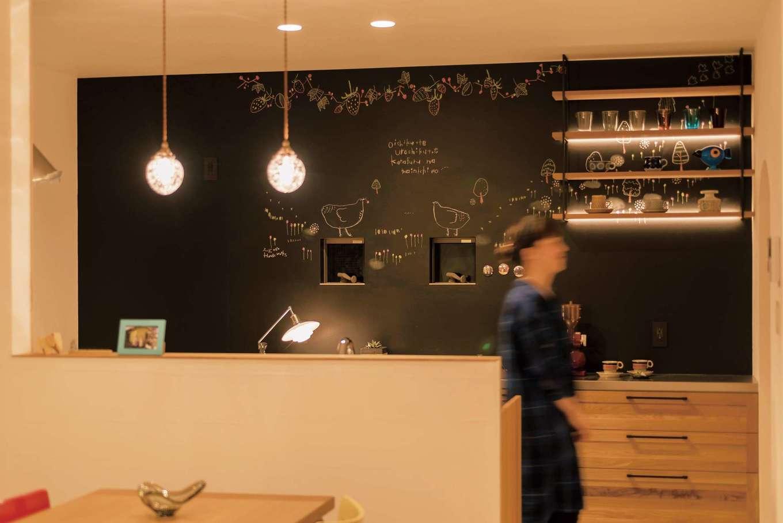 Hands Works(ハンズワークス)【デザイン住宅、夫婦で暮らす、間取り】黒板&磁石塗料で塗装した壁面には、ふくだのぞみさんのチョークアートが。ウッディなシステムキッチンと、間接照明を仕込んだ吊り下げシェルフがカフェのよう