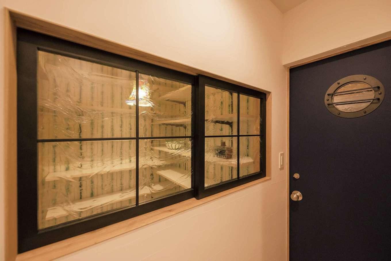 Hands Works(ハンズワークス)【デザイン住宅、夫婦で暮らす、間取り】LDKからバイクガレージに続くドアには、ご主人が希望した丸窓を配した。ガレージ内の照明もマリンランプを取り付け船内のようなイメージでコーディネートしている