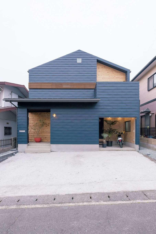 Hands Works(ハンズワークス)【デザイン住宅、夫婦で暮らす、間取り】濃紺のガルバリウムをよろい張りにした、アメリカンテイストの外観。玄関ポーチと2階の一部はレッドシダーを用いてアクセントに。作業スペースや収納棚も確保したバイクガレージは、壁の下地材をそのままにして男前な空間に