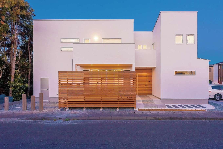 真っ白な外壁に玄関とウッドデッキの木の質感が映える。外構も合わせてデザイン