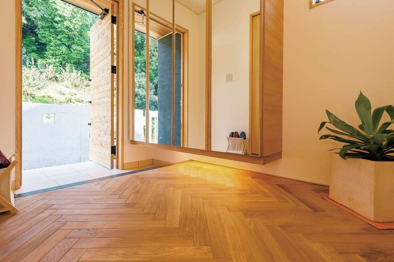 玄関のフロアはヘリンボーン模様に。収納面をすべて鏡にして広くみせる工夫も