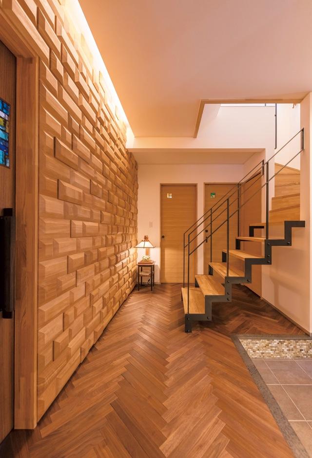 職人の技術の粋を結集した玄関ホール。床はヘリンボーン張り、上がりかまちはアイアンで縁取っている
